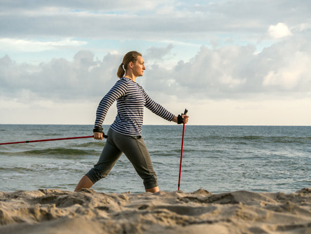 Young woman practising Nordic walking along the beach photo