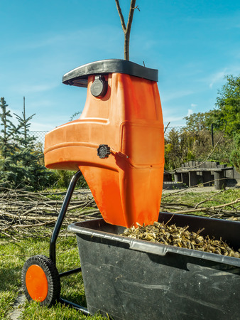 Electric wood shredder with wood chips used for garden mulching