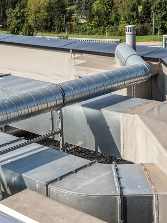 venting: Installation of steel air conditioning duct pipes on the industrial building roof top