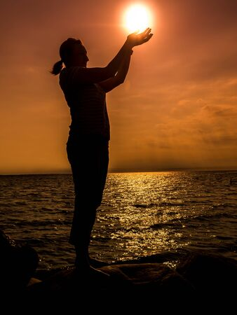 Silhouette of young woman standing by the seashore holding the rising sun over orange sky photo