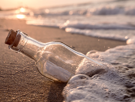 ashore: Message in the bottle washed ashore against the Sun setting down