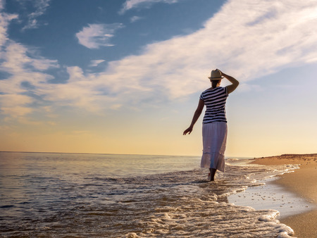 Young woman wearing hat and white skirt strolling along the beach towards the rising Sun photo