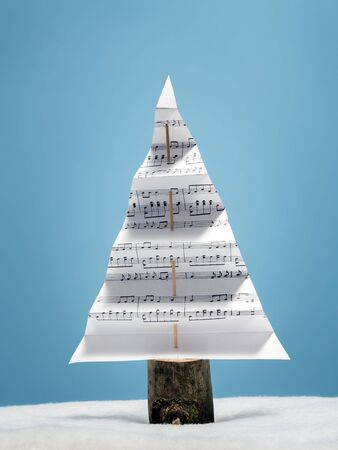 Paper christmas tree with christmas carol notes over light blue background
