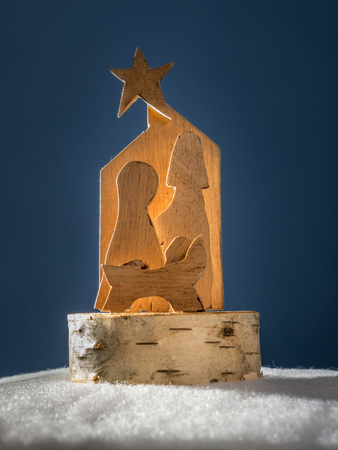 plywood: Christmas crib cut out from plywood over dark blue background