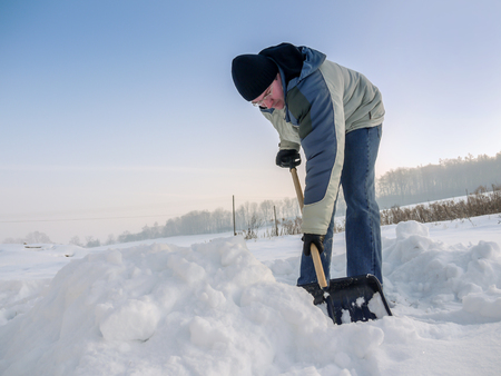 snowbank: Man plowing his backyard with shovel after heavy snowing