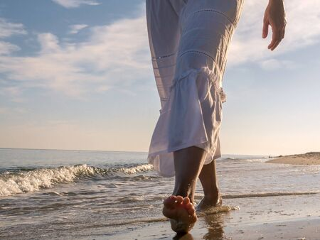Closeup of woman wearing white skirt strolling barefooted along the beach Stock Photo