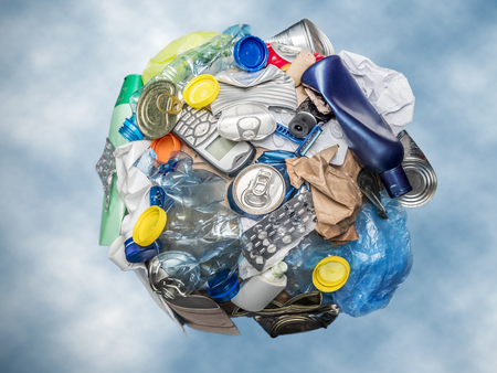 Sphere as Planet Earth formed from assorted domestic waste over blue sky Stock Photo