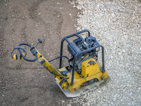 Old yellow plate compactor on aggregate bed