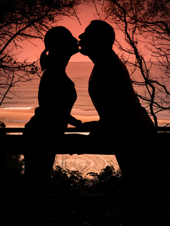 Silhouettes of young couple kissing against sunset sky photo