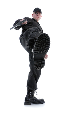 Policeman wearing black uniform making a kick, shot on white Stock Photo