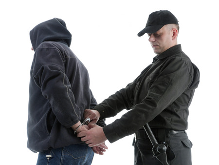 Policeman handcuffing hooded man, shot on white Stock Photo