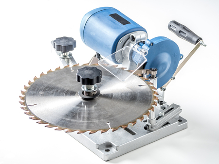 Portable electric saw blade sharpener with attached saw blade shot on white Banco de Imagens