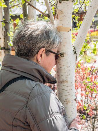 Senior lady hugging white birch tree trunk
