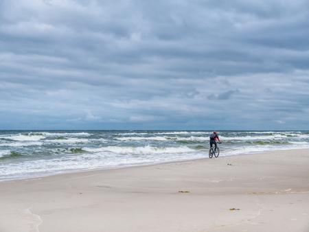 Biker biking along the sandy beach