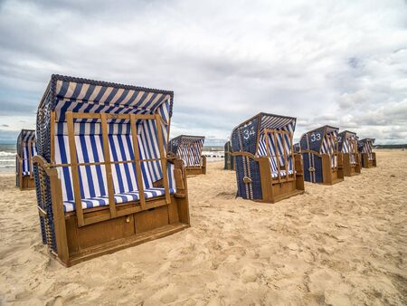 Empty roofed wicker beach chairs on sandy beach in Ustka resort, Baltic sea, Poland  clear sign that summer is over