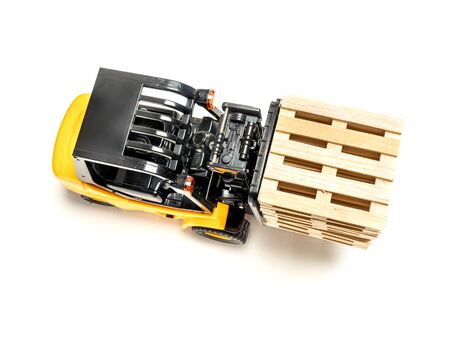 Forklift truck carrying stacked wooden pallets shot from above on white background Stock Photo