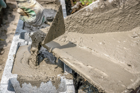 Closeup of mason hand pouring out mortar into concrete shuttering blocks from wheel-barrow Stock Photo