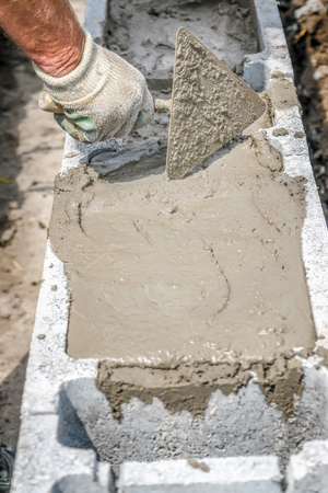 Closeup of mason hand spreading mortar with trowel in concrete shuttering blocks as house foundation Stock Photo