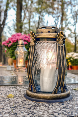 Glass votive candle lit on marble tombstone Stock Photo