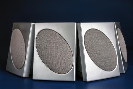 Vier zilveren luidsprekers over donkerblauwe achtergrond Stockfoto