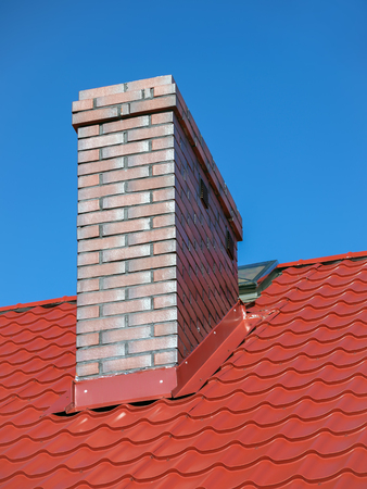 Closeup of red sheet metal roof with brick chimney