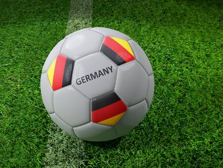 3D rendering of white soccer ball with imprinted German flag colors placed next to the pitch line Stock Photo