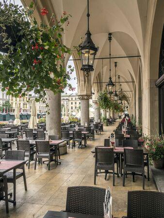 KRAKOW, POLAND - AUGUST 07 2017: Sukiennice arcades with outdoors restaurant tables and chairs, Main Market Square, Krakow, Poland Redakční