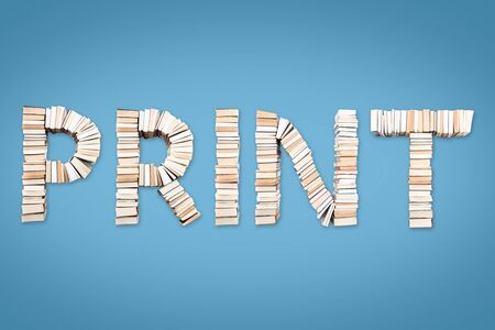 PRINT word formed from books, shot from above on light blue background