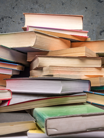 Closeup of pile of old books over gray wall