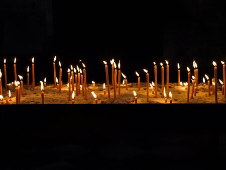 Rows of lit votive candles Stock Photo