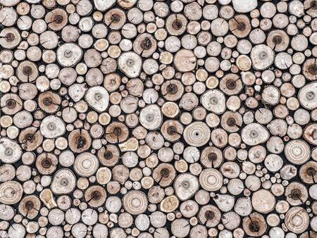 Background of neatly arranged pile of cross-cut wooden logs