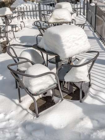 Empty chairs and tables covered with heavy snow cover outside restaurant