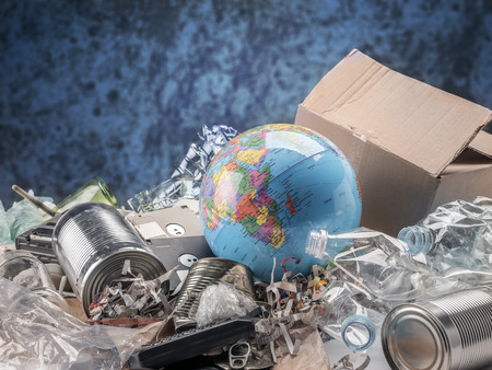 Earth globe dumped onto trash heap - global environmental pollution concept
