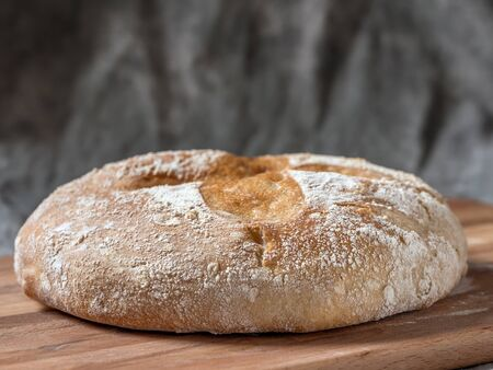 Loaf of home baked bread on wooden cutting board Stock Photo