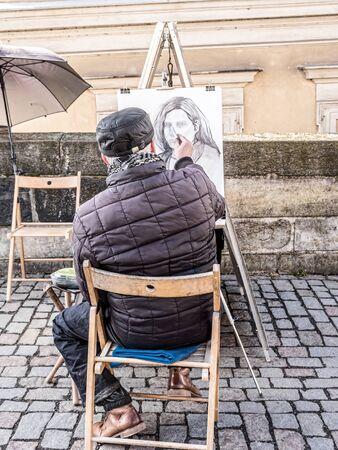 PRAGUE, CZECH REPUBLIC - MARCH 8 2017: Prague caricaturist drawing female portrait on Charles Bridge