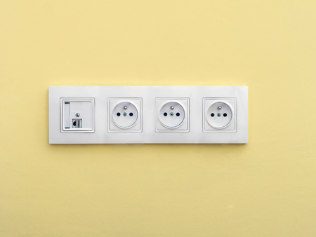 Quadruple wall socket set with internet connection mounted onto yellow wall