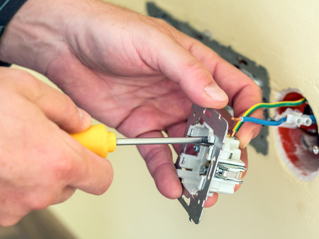 Closeup of electricians hands installing wall socket