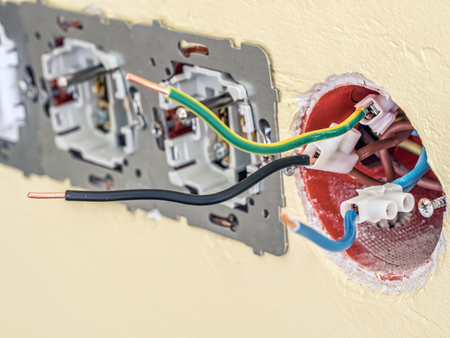 Closeup of partially assembled wall socket with live, neutral and earthing wires protruding from the wall