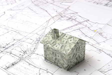 Little 3D cardboard house model wrapped around with American dollar bills on building plan Stock Photo