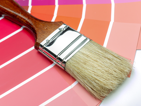 Paint brush on array of paint color swatches Stock Photo