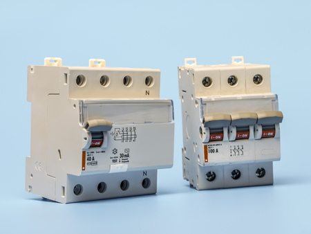 Overcurrent and RCCB breakers, shot over blue background