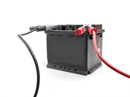 Car battery with two jumper cables attached to the terminals shot on white background Stock Photo