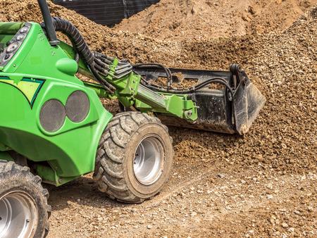Green skid loader loading gravel