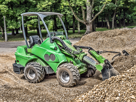 Green skid loader with a load of gravel Stock Photo