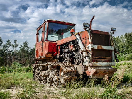 Old broken track tractor abandoned in the field