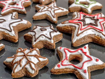Star-shaped seasonal gingerbread cookies with white icing