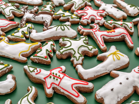 Seasonal shaped gingerbread cookies with white icing on green background