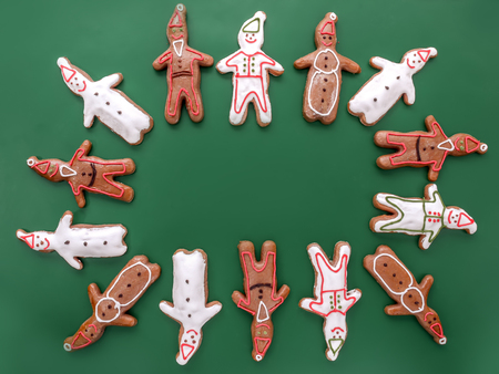 White and brown gingerbread snowman and santa clause-shape figures with color icing shot on green background