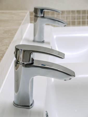 Two bathroom chrome faucets of double white ceramic washbasin
