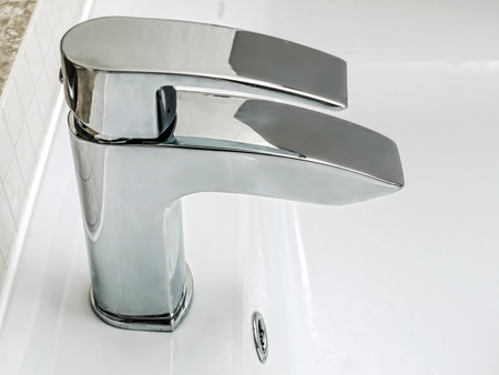 Bathroom chrome faucet of white ceramic washbasin